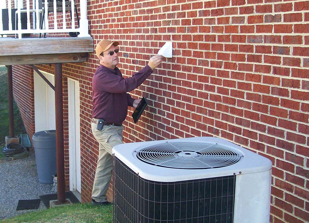 Bill Rupert, one of Tennessee's licensed home inspectors, examining the exterior of a brick house and air conditioning system