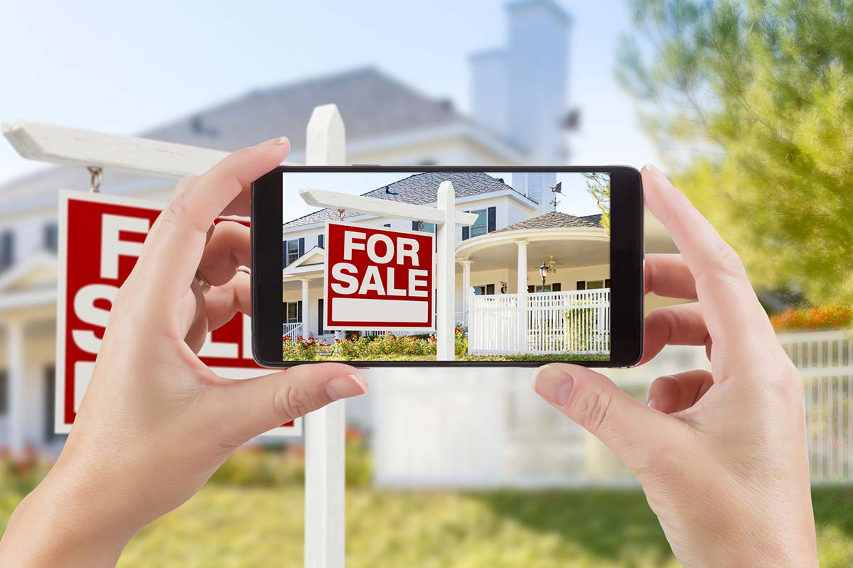 Hands holding up a smartphone and taking pictures of a house for sale after passing thorough pre-listing home inspection services