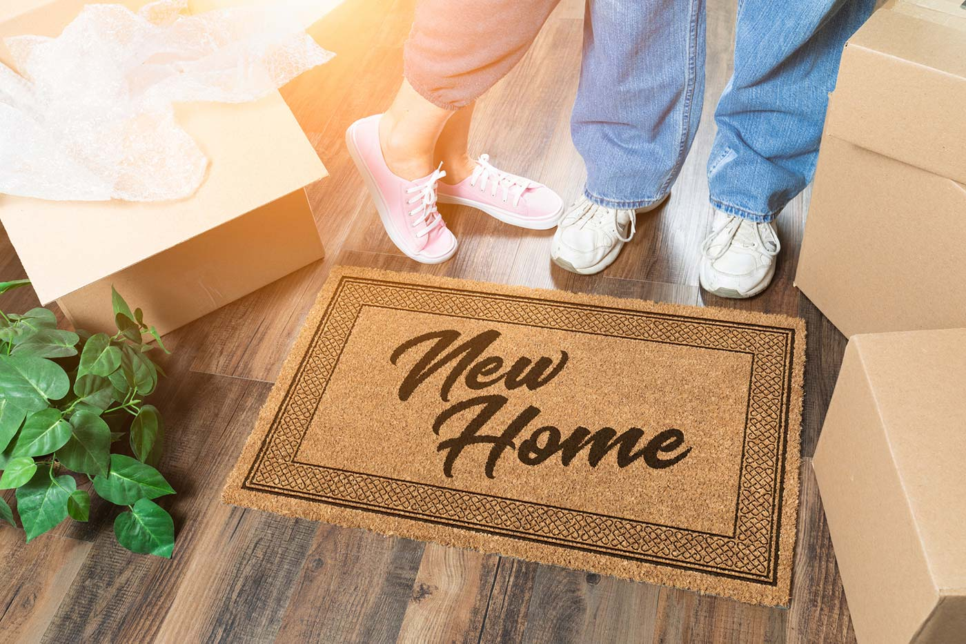 A couple standing next to a New Home welcome mat and moving boxes after receiving thorough home inspection services